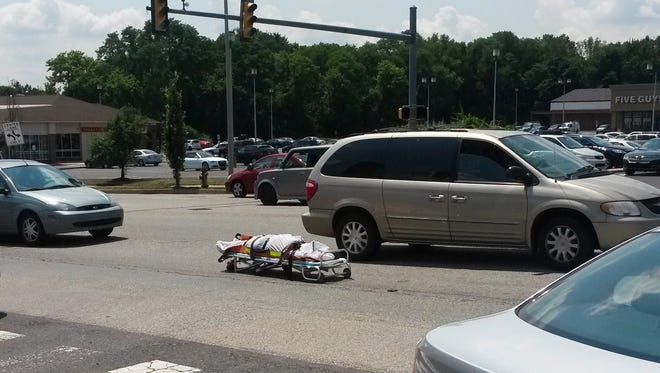 A corpse strapped to a gurney in the middle of an intersection in Feasterville, Pa., awaits pickup on July 11. It had fallen out of a coroner's vehicle.