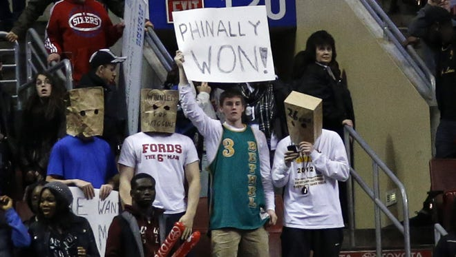 Fans hold signs after the Philadelphia 76ers won an NBA basketball game against the Detroit Pistons, Saturday, March 29, 2014, in Philadelphia. Philadelphia won 123-98, breaking a 26-game losing streak.