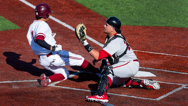 Indiana University catcher Kyle Schwarber (10) concentrates on the throw to home as Stanford University's Alex Blandino (1) slides in safely for the score. Indiana University played Stanford University in the semi-final round of the NCAA Regional Baseball tournament, Saturday, May 31, 2014, in Bloomington, Ind.