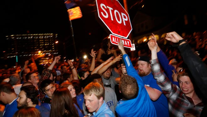 Fans celebrated , by tearing down a stop sign, on State Street, near campus in Lexington, Kentucky's 74-73 win over Wisconsin in the NCAA TournamentÕs Final Four. April 6, 2014