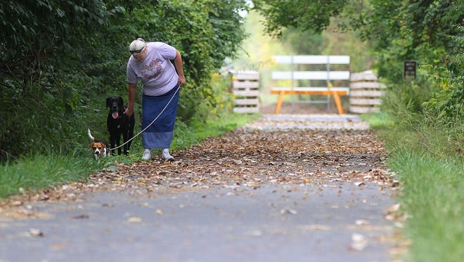 Thena Smith and friends Lexi and Digger walk the Tallgrass Trail up to a construction sign and back on Monday, Sept. 9, 2014. Smith said she and her buddies walk the trail everyday. The trail is closed west of the footbridge for additional paving work. James Miller/The Marion Star