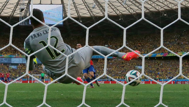 Brazil's goalkeeper Julio Cesar makes a save after Chile's Mauricio Pinilla shot from the penalty spot in the shoot-out of the World Cup round of 16 soccer match between Brazil and Chile at the Mineirao Stadium in Belo Horizonte, Brazil, Saturday, June 28, 2014.