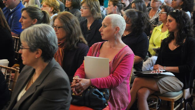 Carol Curcio, center, of Poughkeepsie, whose son is a heroin addict and in prison, listens to Dr. Kari Reiber, the Dutchess County commisioner of health, during Monday's forum.