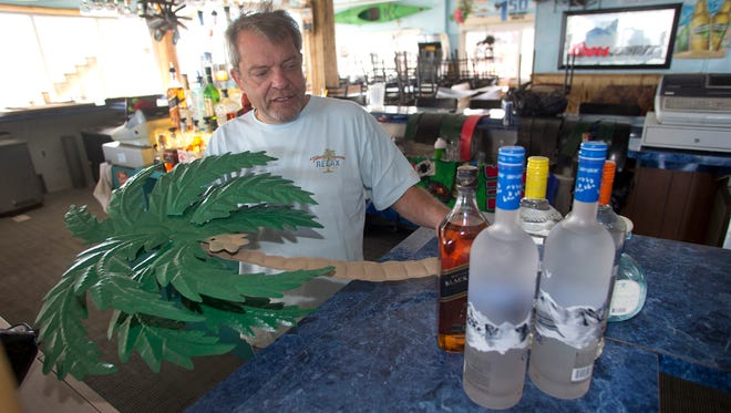 At the Beachcomber Bar and Grill in Seaside Heights, N.J., owner Michael Carbone Sr. looks over a metal palm tree that was restored after the Sept. 12 Seaside fire on the boardwalk. The owner attributes not losing the building completely to a sprinkler system.