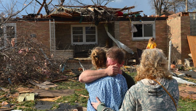 Ray Baughman embraces family shortly after his home was destroyed by a tornado in Pekin, Ill.