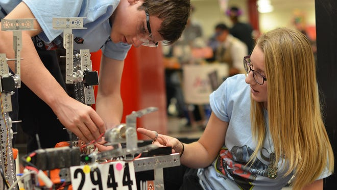 Robert Gauthier and Remy Jesionka adjust their robot for a high school competition in Flagstaff, Ariz., in November.