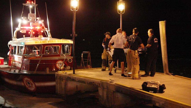 Emergency workers carry an injured person on a stretcher July 4 after three boats collided near a Miami marina after a fireworks display. Four were killed and a dozen others injured.