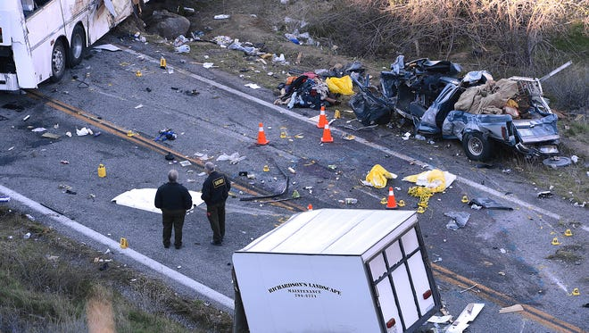 In this Feb. 4, 2013, photo, investigators work the scene where a tour bus collided with a pickup truck on Highway 38 north of Yucaipa, Calif., killing eight people. Federal regulators ordered the tour bus operator, National City, Calif.-based Scapadas Magicas LLC,  to immediately stop operating because its buses weren't properly maintained or inspected and its drivers weren't properly vetted for qualifications.