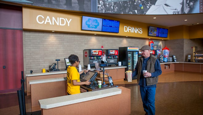 Middletown resident Roger Blanchard brings his popcorn and drink to cashier Vanessa Stone at Westown Movies in Middletown. A bill that would allow beer, wine and liquor sales at theaters is pending.