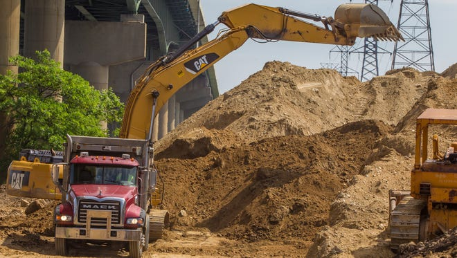 A contractor works to clear dirt from under the I-495 bridge Wednesday. The piles could have had a role in compacting soft soils beneath the surface.