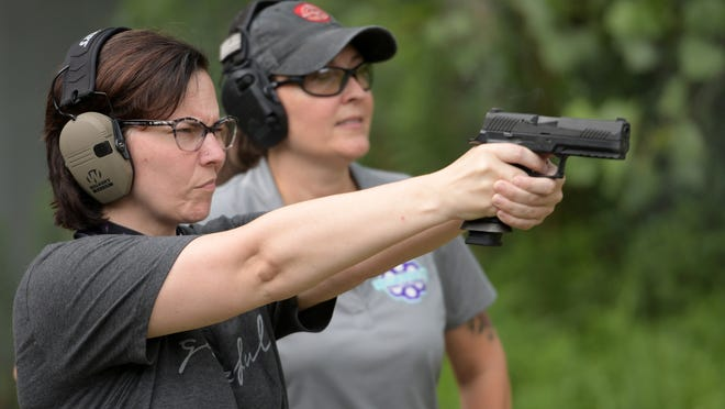 Julie Reno of Holden shoots a SIG Sauer P320 9 mm pistol with instructor Lakasha Robbins, right, Thursday at the Worcester Pistol & Rifle Club in Boylston.