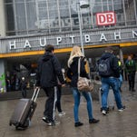 Travellers and pedestrians walk toward the central railway station in Munich, Germany, Jan. 1, 2016.