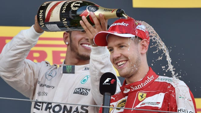 Mercedes driver Lewis Hamilton and Ferrari driver Sebastian Vettel celebrate on the podium in Japan in 2015.