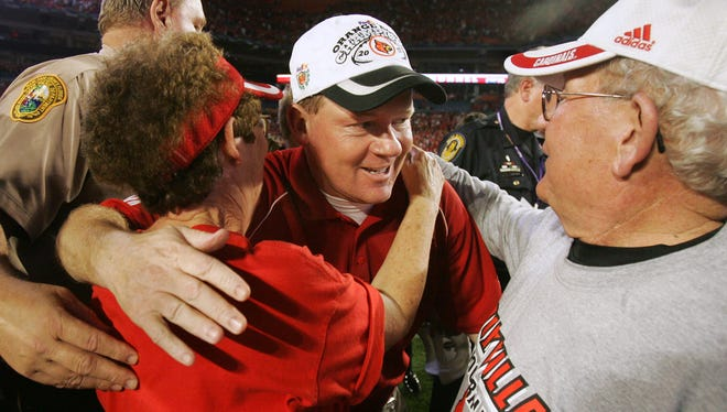 Louisville coach Bobby Petrino, center, received congratulatory hugs from his parents, Bob Petrino Sr. and Patsy, after the 2006 Cards' Orange Bowl victory completed a historic 12-1 season.