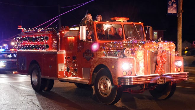 Santa Claus arrives in Dagsboro on the back of a firetruck.