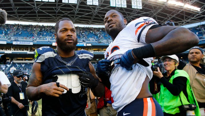 Seahawks defensive end Michael Bennett , left, and Bears tight end Martellus Bennett take off their jerseys following a 26-0 Seattle victory at CenturyLink Field on Sunday.
