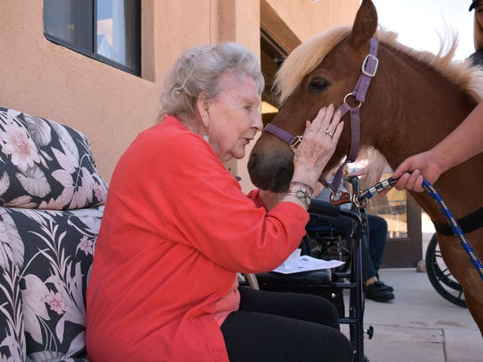 Leona Richardson, a Casa Arena Blanca resident, takes a moment to pet Red.