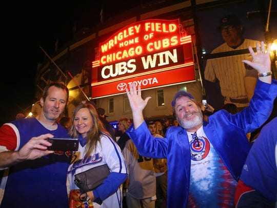 Chicago Cubs fans including Joe Downs (right) celebrate outside of Wrigley Field after game four of the NLDS against the St. Louis Cardinals.