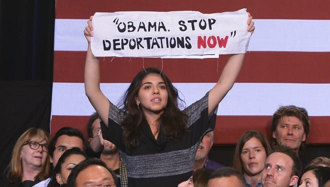 A protestor holds up a banner as a guest beside her reaches to pull it away as President Obama speaks on immigration reform at the Copernicus Community Center Tuesday in Chicago.