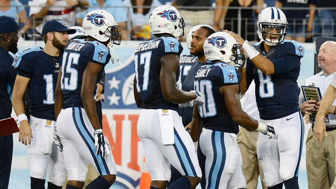 Tennessee Titans quarterback Marcus Mariota (8) congratulates teammate Bishop Sankey (20) after the Tennessee Titans scored a touchdown against the Minnesota Vikings in the first half of a preseason NFL football game Thursday, Sept. 3, 2015, in Nashville, Tenn. Also coming to the sideline are Justin Hunter (15) and Dorial Green-Beckham (17).