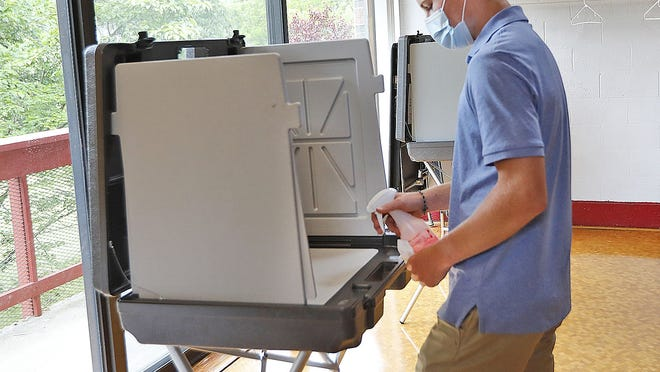 Recent Milton High graduate Bobby Carew,18, cleans each voting booth after use at the Cunningham Community Center in Miton, during town elections on Tuesday.