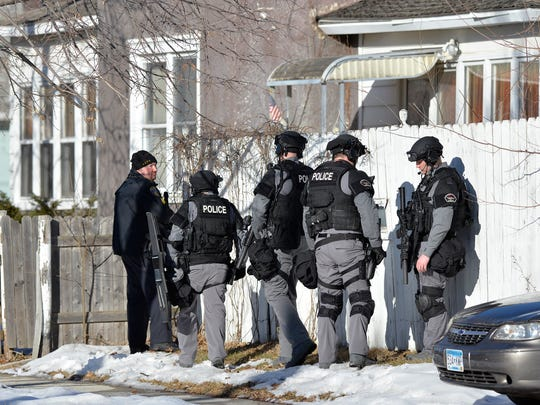 St. Cloud Police Department officers and S.W.A.T. team members wait on the scene of a standoff Tuesday afternoon at a home on the southeast corner of the intersection of 19th Avenue North and Third Street.