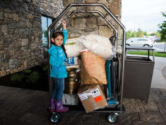 Mariel Poole, 5, stands next to donations her father,