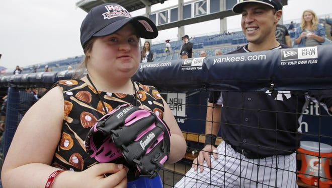 Cappy Farrell, left, who says she wants to pitch for the Yankees, gets a laugh from    first baseman Mark Teixeira before an exhibition game against the Marlins in Tampa, Fla., Friday. Farrell, who participates in the Odessa, Fla.-based Quantum Leap Farm programs for mentally and physically disabled individuals, attended Yankees batting practice Friday before the organization was honored prior to the start of the game.