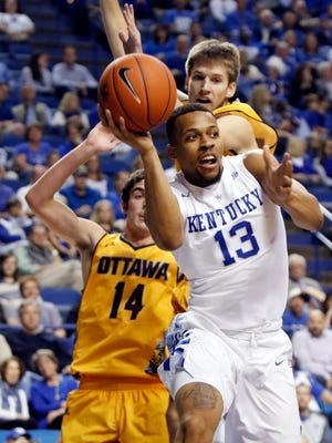 Kentucky's Isaiah Briscoe (13) looks for an open teammate while defended by Ottawa's Logan Bullinger (14) and Riley Falk during an NCAA college basketball exhibition game Monday, Nov. 2, 2015, in Lexington, Ky.
