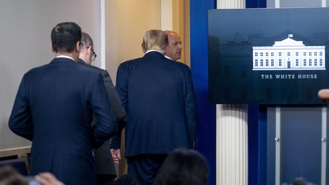 President Donald Trump is asked to leave the James Brady Press Briefing Room by a member of the U.S. Secret Service during a news conference at the White House, Monday evening.