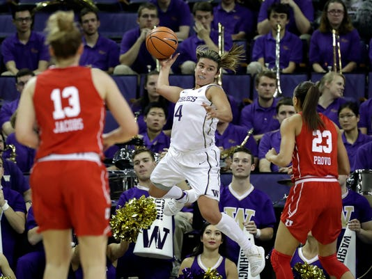 Washington's Amber Melgoza (4) leaps in an effort to save a ball headed out of bounds as Utah's Megan Jacobs (13) and Daneesha Provo watch during the first half of an NCAA college basketball game Friday, Jan. 5, 2018, in Seattle. (AP Photo/Elaine Thompson)