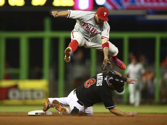 Philalphia Phillies shortstop Freddy Galvis (13) leaps over Miami Marlins' Jeff Mathis (6) at second on a double play hit into by Reed Johnson during a seventh inning of a baseball game in Miami, Wednesday, Sept. 24, 2014. (AP Photo/J Pat Carter)