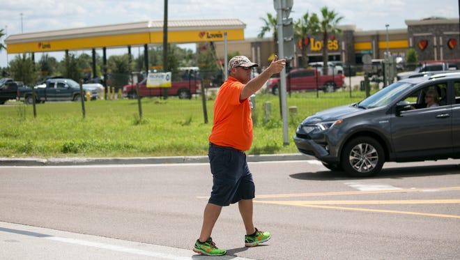 An employee at Love's in North Fort Myers off Interstate 75 directs traffic to allow tractor trailers to get in among the two-hour-long line of cars waiting for gas on Wednesday. The station was stocking up on gas all day long.