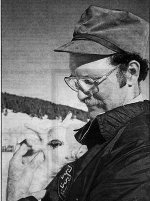 Where it all started. Mel Jackson is shown cuddling a piglet in this 1985 photo from the Great Falls Tribune. The accompanying article sparked the interest of Becky Smith, who married Jackson little more than a year later.