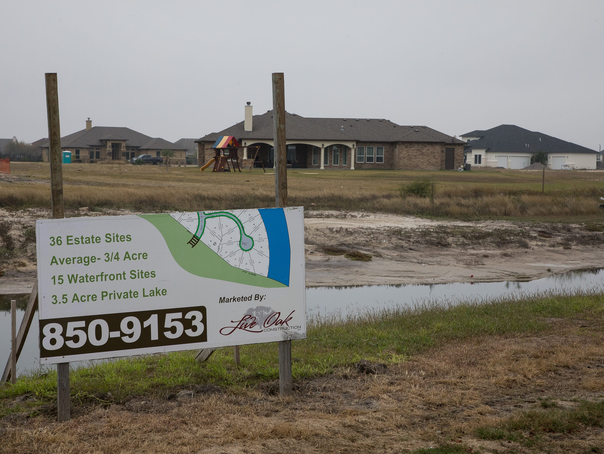 A sign advertises available waterfront properties along Oso Creek. Portions of the creek are recognized in proposed flood maps as being at higher-risk than shown in the 1985 maps.