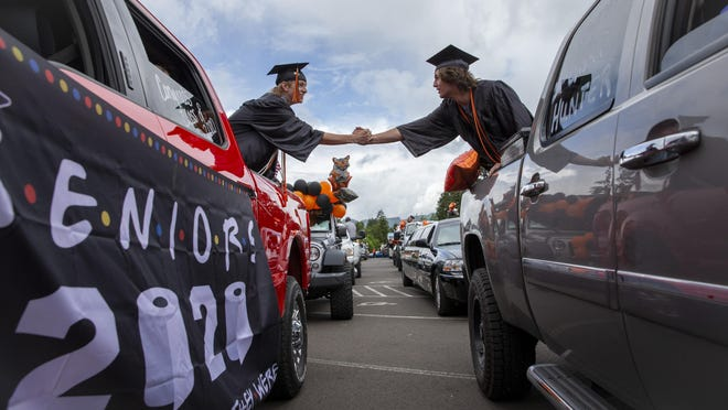 Mohawk High School seniors Dalton Martin and Hunter Carter shakes hands from the backs of their trucks as they stage in the parking lot to receive their diplomas as graduates of the Class of 2020. The traditional graduation at the school was canceled due to COVID-19 so seniors had a drive-through celebration that went through Marcola. [Andy Nelson/The Register-Guard] - registerguard.com