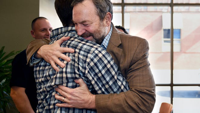 Barry Kolar, right, embraces and thanks former YMCA aquatics coordinator Christian Buitron for giving CPR to Kolar after he went into cardiac arrest at the downtown YMCA.