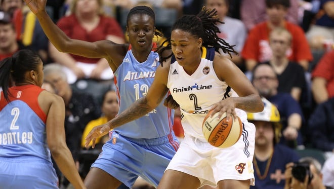 Indiana Fever guard Erlana Larkins (2) runs with the ball as Atlanta Dream guard Alex Bentley (2) and forward Aneika Henry (13) defend at Bankers Life Fieldhouse, Sept. 29, 2013.