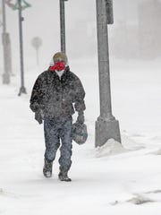 Chris Barrett walks in low visibility conditions in downtown Mandan, N.D., during the Christmas Day blizzard on Sunday, Dec. 25, 2016. Most of the Dakotas and southwest Minnesota had turned into a slippery mess due to freezing rain Sunday morning before snow arrived later in the day as temperatures fell.