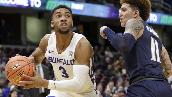 Buffalo's Jayvon Graves, a St. Vincent-St. Mary graduate, drives past the University of Akron's Channel Banks during the 2019 Mid-American Conference Tournament.