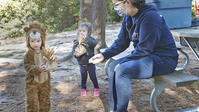 Casey Simko at right hands out Halloween goody bags to Alexandra McCann,2 in her lion suit and Journi Favreau,2.5 after the walk through the woods.  The Rockland Youth Commission sponsored a Halloween walk through Hartstuff Park and read children's Halloween stories on Monday October 19, 2020  Greg Derr/ The Patriot Ledger