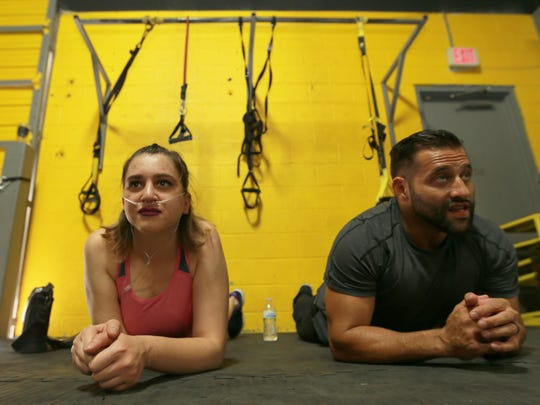 Dima Azzam and trainer Gabino Gonzalez perform planks during a workout