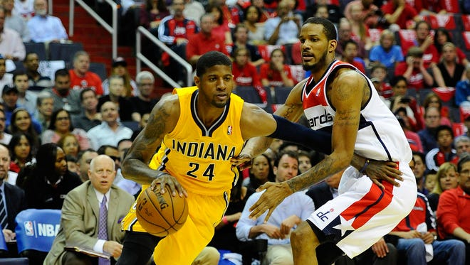 Indiana Pacers small forward Paul George (24) dribbles the ball as Washington Wizards small forward Trevor Ariza (1) defends during the first half in game four of the second round of the 2014 NBA Playoffs at Verizon Center.
