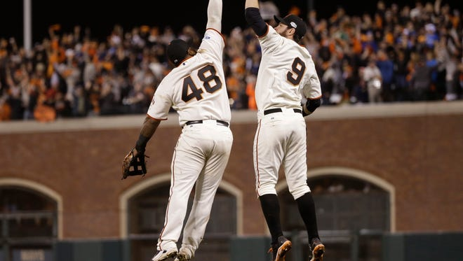 San Francisco Giants Pablo Sandoval, left, leaps up to high-five Brandon Belt after defeating the Kansas City Royals 11-4 in Game 4 of the World Series Saturday  in San Francisco.