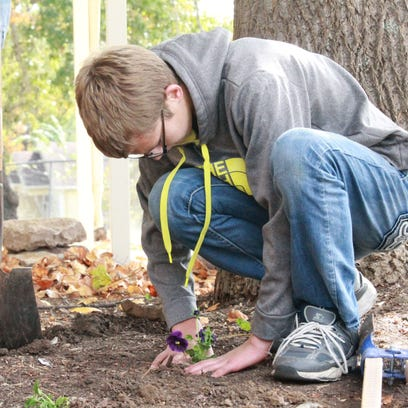 Jason Downs, 16, spends Monday, Oct. 12, 2015 planting