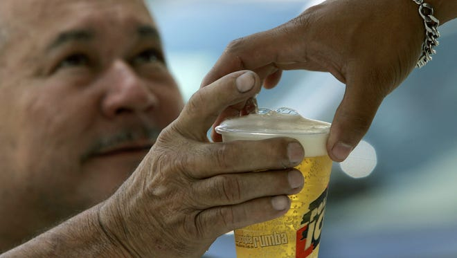 A man buys beer in an outdoor bar at a Caracas auto show in Venezuela on Oct. 7, 2007.