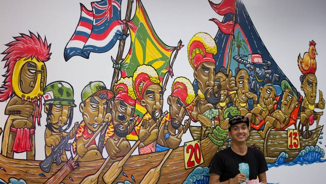 "A mural along one of the walls at Hafaloha, called ""The Big Race."" Elmaro Nazareta, graphic artist and designer at Hafaloha, is seen here standing in front of the mural."