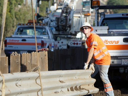 Garred Oldham of Caltrans maneuvers a section of guardrail