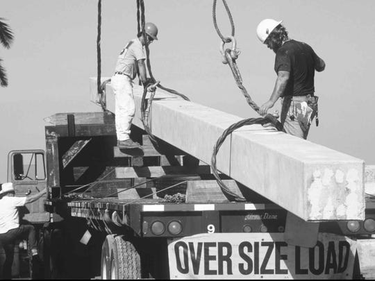 Stanley Sakowski, left, and Bill Hines unload a 92-foot concrete piling during construction of the Midpoint Memorial Bridge in 1996.