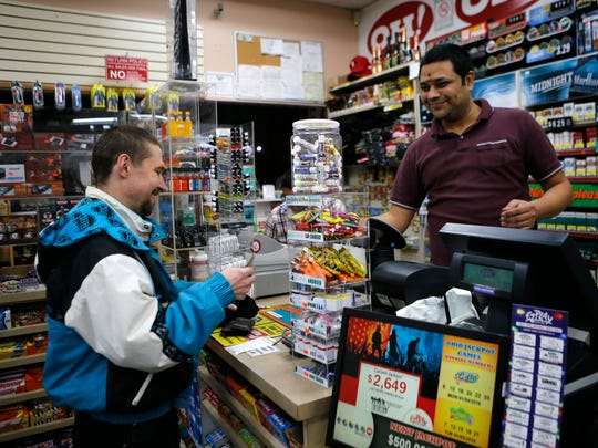 Carl Harper, 45, of Delhi, purchases a Powerball lottery ticket from Sudhakar Gundaji at Garfield Mini-Mart in downtown Cincinnati on Wednesday, Jan. 6, 2016. Wednesday's Powerball jackpot is an estimated $500 million.